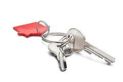 庄园概念、红色钥匙圈和钥匙在被隔绝的背景 免版税库存图片