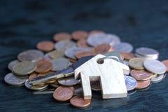 庄园概念,与房子标志的keychain,钥匙在一枚黑背景硬币被安置 免版税库存照片