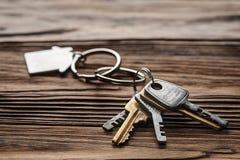 庄园概念,与房子标志,在木背景的钥匙的keychain 库存照片