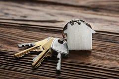 庄园概念,与房子标志,在木背景的钥匙的keychain 免版税图库摄影