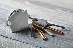 庄园概念,与房子标志,在木背景的钥匙的keychain 免版税库存图片