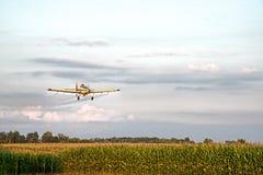 庄稼喷粉器喷洒的麦地 免版税库存照片