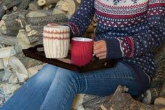 庄稼观点的有冬天成套装备的年轻妇女,拿着一个杯子热的饮料 库存图片