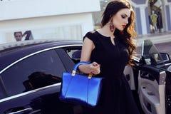 庄重装束的妇女与袋子,摆在一辆豪华汽车旁边 库存图片