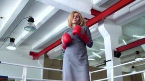 庄重装束的妇女和拳击手套显示专业命中在照相机 影视素材