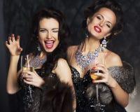 庄重装束的妇女用香槟-夜生活 库存照片
