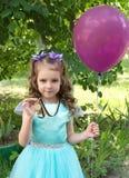 庄重装束的漂亮的孩子女孩与金牌和空气轻快优雅 免版税库存图片