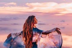 庄重装束的美丽的少妇在日落的海滩 免版税库存照片