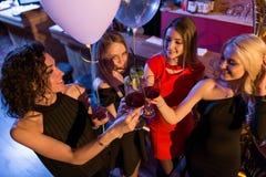庆祝一个假日的可爱的年轻女性朋友站立与杯在时髦酒吧的酒 免版税库存图片