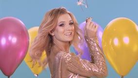 庆祝一个生日一个年轻金发碧眼的女人的画象 她拿着一个闪烁发光物并且微笑着,获得乐趣 影视素材
