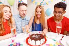 庆祝一个生日的青年人坐在 免版税库存图片