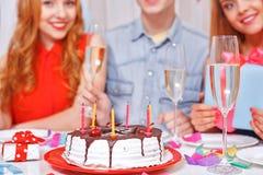 庆祝一个生日的青年人坐在 免版税图库摄影