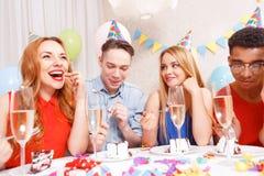 庆祝一个生日的青年人坐在 免版税库存照片