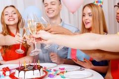 庆祝一个生日的青年人坐在 库存图片