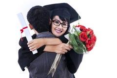 庆祝与她的男朋友的妇女毕业典礼举行日 库存图片