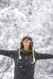 庆祝与她的胳膊的少妇冬天广泛被涂 免版税库存图片