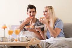 庆祝与早餐的年轻夫妇在床上 免版税图库摄影