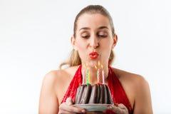 庆祝与蛋糕和蜡烛的妇女生日 免版税库存图片