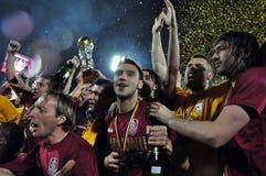 庆祝与金黄杯子的足球运动员 库存照片