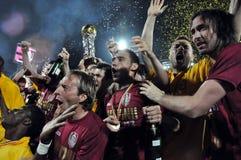庆祝与金黄杯子的足球运动员 免版税库存照片
