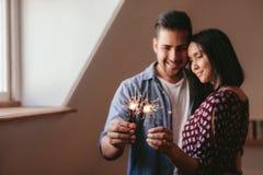 庆祝与闪烁发光物的美好的年轻夫妇 免版税库存图片