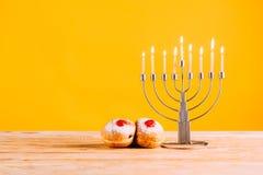 庆祝与menorah和油炸圈饼的光明节在木桌面 图库摄影