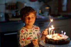 庆祝他的可爱的愉快的白肤金发的小孩男孩7生日 免版税库存图片