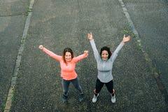 庆祝健身锻炼目标的两名成功的运动的妇女 免版税库存图片