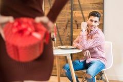 庆祝华伦泰与晚餐的年轻愉快的夫妇` s天在 免版税库存照片