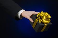 庆祝和礼物题材:拿着一件专属礼物的一套黑衣服的一个人被包装在有金丝带的,花花公子一个黑匣子 免版税库存照片