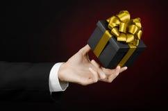 庆祝和礼物题材:拿着一件专属礼物的一套黑衣服的一个人被包装在有金丝带的,花花公子一个黑匣子 免版税库存图片