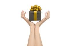庆祝和礼物题材:递拿着礼物被包裹在有金丝带和弓的,最美丽的礼物一个黑匣子 库存照片