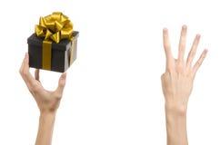 庆祝和礼物题材:递拿着礼物被包裹在有金丝带和弓的,最美丽的礼物一个黑匣子 图库摄影