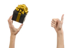 庆祝和礼物题材:递拿着礼物被包裹在有金丝带和弓的,最美丽的礼物一个黑匣子 免版税库存图片
