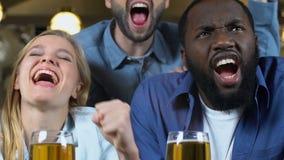 庆祝喜爱的体育队目标使叮当响的啤酒杯的年轻朋友在客栈 影视素材