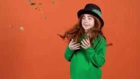 庆祝圣帕特里克在橙色墙壁上的女孩少年` s天投掷金黄硬币 股票视频