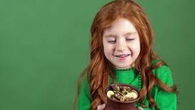 庆祝圣帕特里克` s天绿色墙壁背景的女孩红色头发看在有金子的罐 股票录像
