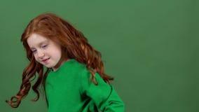 庆祝圣帕特里克` s天绿色墙壁背景的女孩红色头发转过来 股票录像