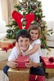 庆祝圣诞节愉快的姐妹的兄弟 免版税库存图片
