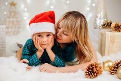 庆祝圣诞节或新年假日的家庭母亲和儿子 免版税图库摄影