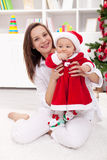 庆祝圣诞节的女婴和母亲 库存照片