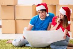 庆祝圣诞节的年轻家庭在新的家 免版税图库摄影