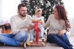 庆祝圣诞节的时髦的家庭在屋子里在圣诞树附近 免版税图库摄影