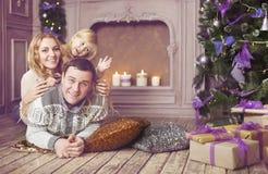 庆祝圣诞节的时髦的家庭在屋子里在圣诞节附近 免版税库存图片
