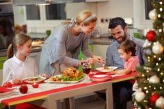 庆祝圣诞节-母亲服务火鸡的家庭 库存照片