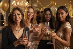 庆祝在党的女性朋友做多士对照相机 免版税库存图片