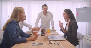 庆祝在办公室的四快乐的collleagues画象户内 在对的玻璃的商人喜讯说 影视素材