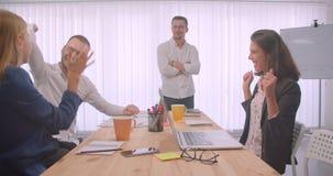 庆祝在办公室的四快乐的collleagues画象户内 对的商人关于的喜讯说 股票视频
