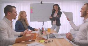 庆祝在办公室的四快乐的collleagues画象户内 得出在whiteboard的女实业家一张图表 股票录像