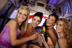 庆祝在大型高级轿车的俏丽的女孩 免版税库存图片